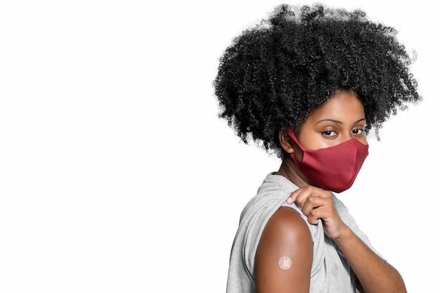 Adolescente nero che indossa una maschera protettiva contro covid19 con un sorriso sul viso mostra il vaccino