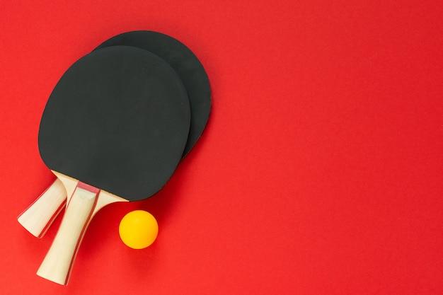 Racchette da ping pong da tennis nere e palla arancione isolate su un rosso