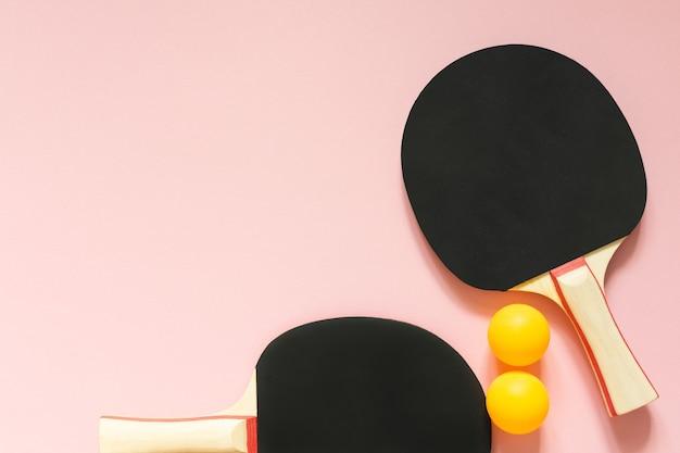 Racchette da ping pong da tennis nere e palline arancioni isolate su uno sfondo rosa, attrezzature sportive per il tennis da tavolo