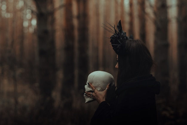 La strega terribile nera con un teschio nelle mani di un uomo morto esegue un rituale mistico occulto nella foresta