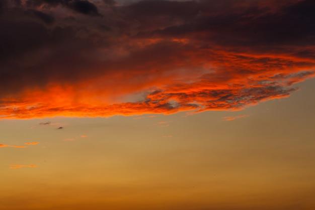 Nuvole temporalesche nere al tramonto. tramonto arancione brillante e nuvole scure.