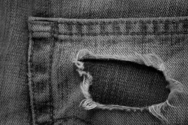 Sfondo nero tasca denim strappato
