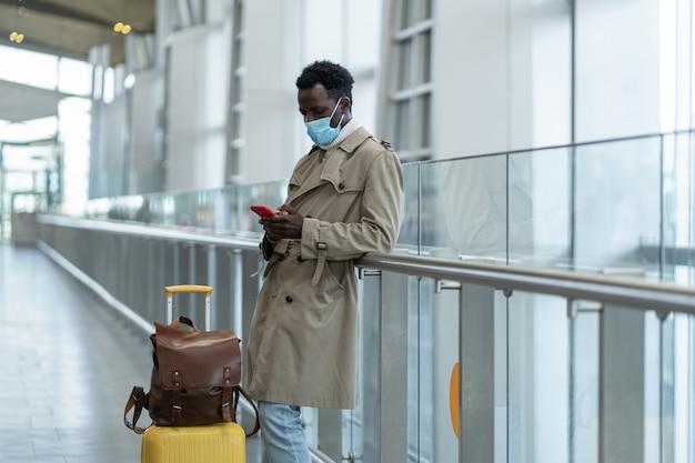 L'uomo viaggiatore nero nel terminal dell'aeroporto indossa una maschera per proteggersi dalla pandemia di coronavirus covid