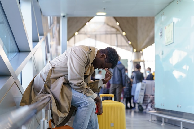 L'uomo viaggiatore nero ha dormito troppo, ha perso l'aereo seduto nel terminal dell'aeroporto. vista laterale.