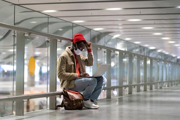 Uomo viaggiatore nero indossa la maschera per il viso seduto nel terminal dell'aeroporto vuoto