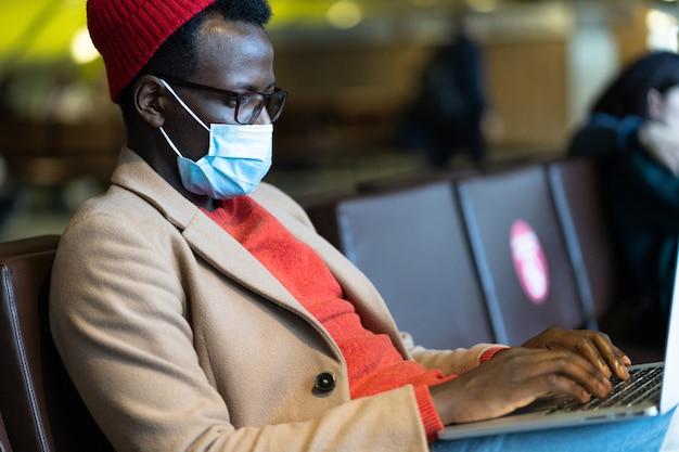 L'uomo viaggiatore nero indossa una maschera protettiva per il viso, seduto in aeroporto, funziona in remoto sul laptop. covid-19