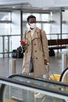 Il viaggiatore nero con la valigia va alla scala mobile nel terminal dell'aeroporto indossando una maschera facciale