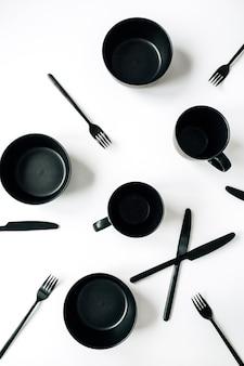 Stoviglie nere alla moda: forchette, coltelli, tazze, ciotole sulla superficie bianca. vista piana laico e dall'alto