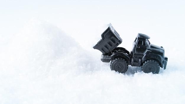 Un camion nero sta sgombrando la neve durante la pulizia dell'autocarro con cassone ribaltabile