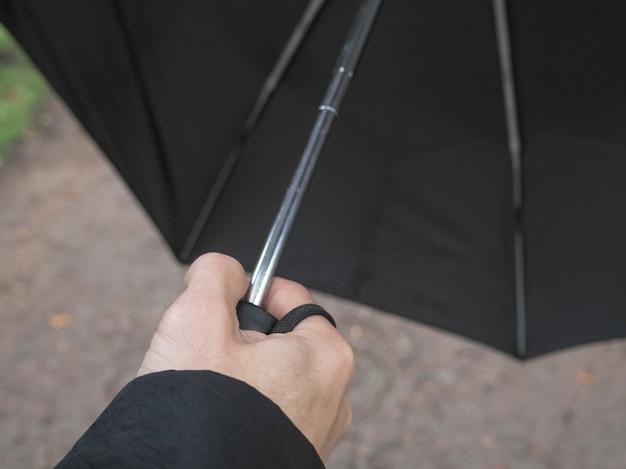 Un ombrello nero nella mano di un uomo
