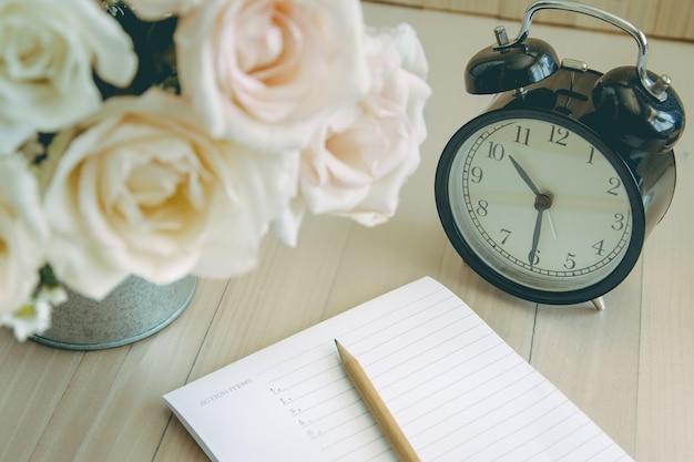 Orologio vintage nero con taccuino e matita