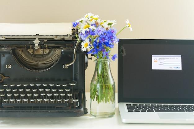 Macchina da scrivere vintage nera e laptop moderno sulla tavola di legno