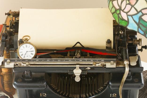 Macchina da scrivere vintage nera con nota di carta di età in bianco con orologio da tasca antico