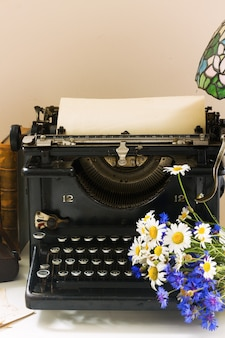Macchina da scrivere vintage nera con libri sulla tavola di legno con fiori
