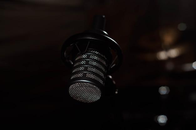 Il microfono vocale nero è posizionato nella stanza dello studio di registrazione del suono utilizzando la radio di produzione di podcast o lo strumento del cantante principale che significa eseguire un'onda audio musicale