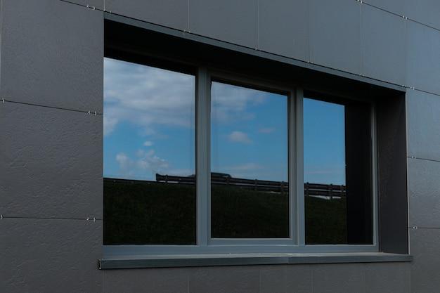 Parete nera e grandi finestre di edificio alto con la riflessione del cielo