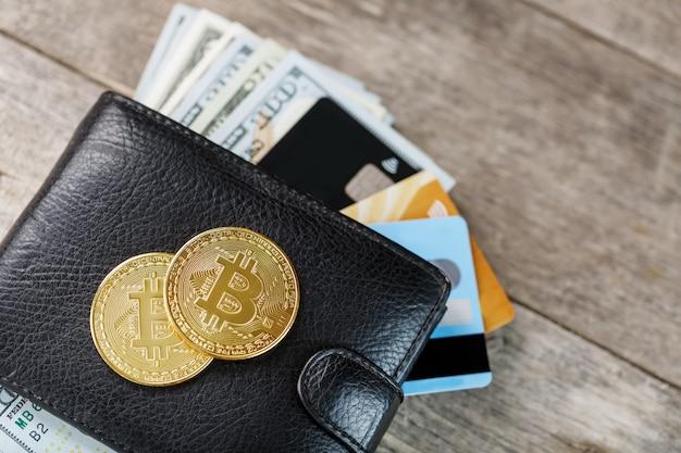 Portafoglio nero con banconote, carte elettroniche e bitcoin su legno.