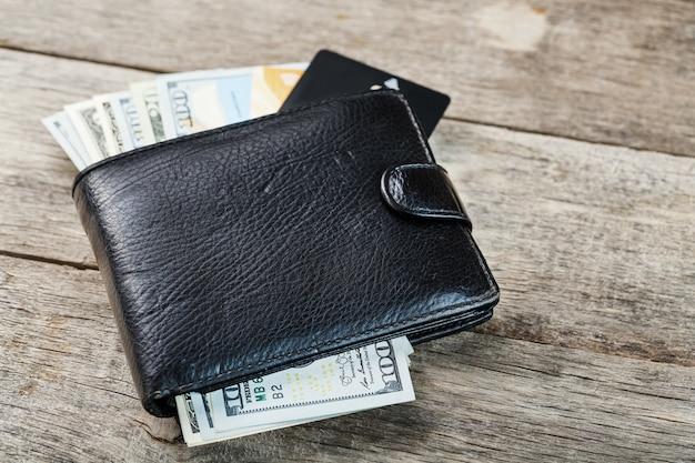 Portafoglio nero con banconote, carte elettroniche e bitcoin su una parete di legno. simbolo di prosperità e prosperità.