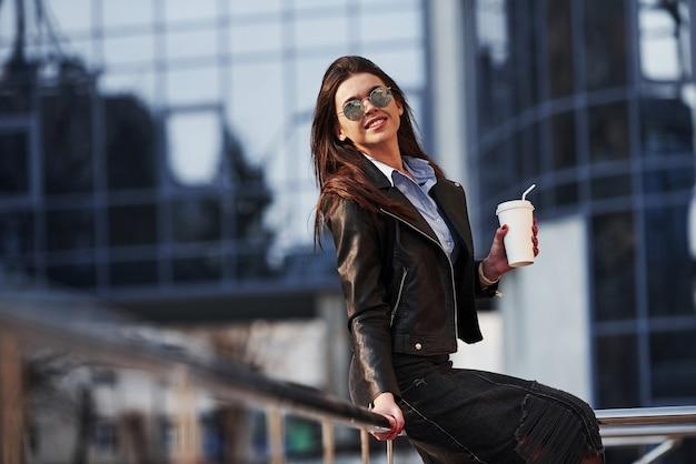 In abbigliamento nero. la giovane bella ragazza in vestiti caldi ha passeggiata in città durante il suo tempo di fine settimana