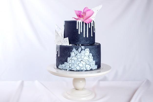 Torta nunziale nera decorata con cioccolato bianco e fiore dell'orchidea