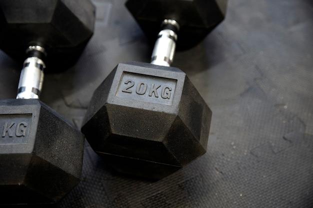 Pesi neri sull'attrezzatura di bodybuilding della pavimentazione di gomma nera 20 chilogrammi primo piano