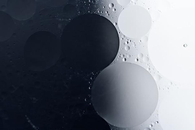 Sfondo astratto bianco e nero di gocce di olio a forma di cerchio sulla superficie dell'acqua, struttura di arte
