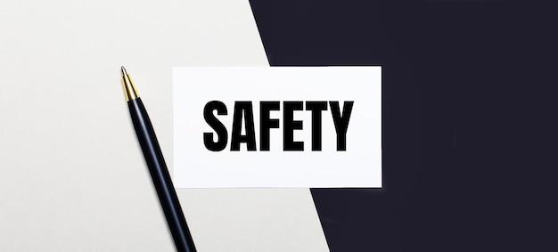 Su uno sfondo bianco e nero si trovano una penna e una carta bianca con il testo safety