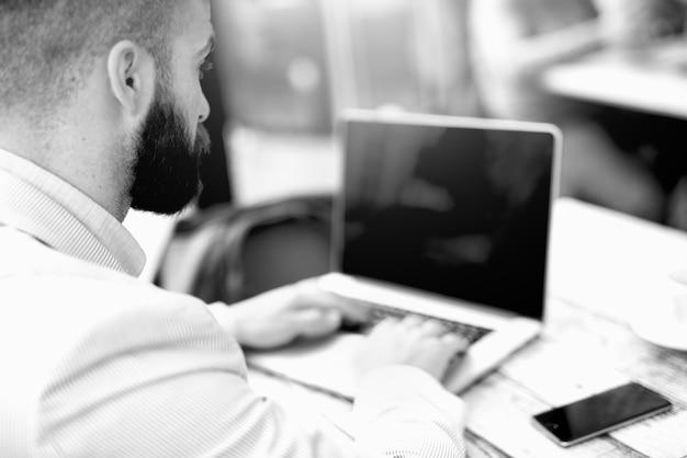 Uomo in bianco e nero di affari che scrive sul computer portatile.