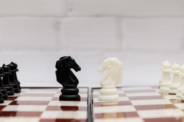 Cavalieri di scacchi in bianco e nero uno di fronte all'altro su una scacchiera