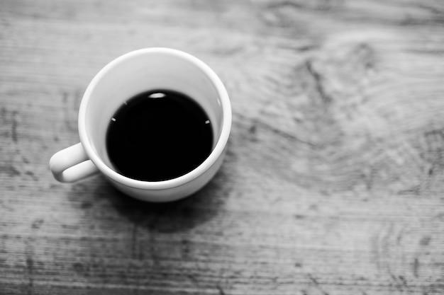 Tazza di caffè in bianco e nero su fondo di legno