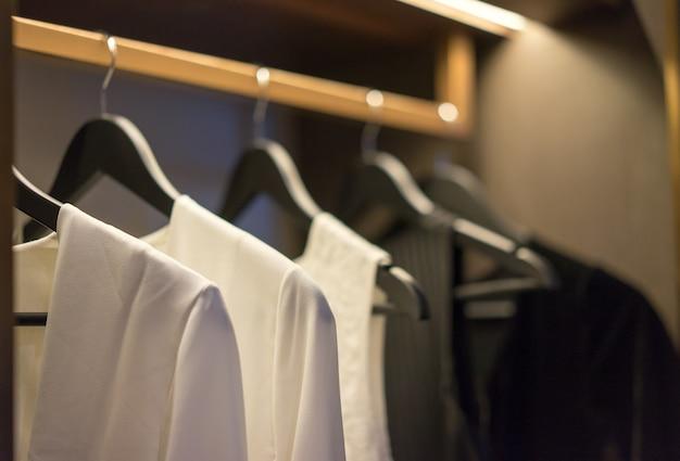 Vestiti di tono di colore in bianco e nero che appendono sulla ferrovia in un guardaroba, interior design.