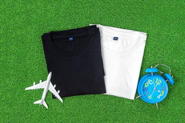 T-shirt in cotone bianco e nero messa sull'erba verde con aeroplano e sveglia