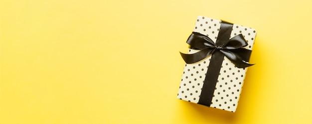 Confezione regalo in bianco e nero su giallo. lay piatto