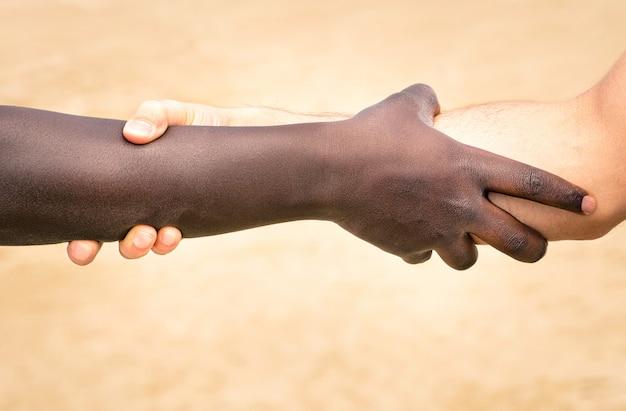 Mani in bianco e nero nella stretta di mano moderna per mostrarsi reciprocamente amicizia e rispetto