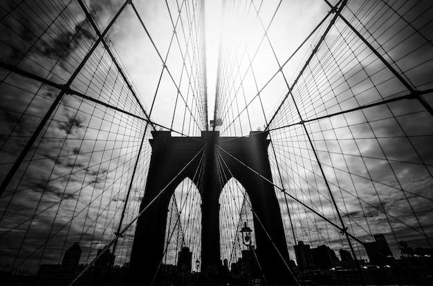 Immagine in bianco e nero della sagoma del ponte di brooklyn con un cielo drammatico e raggi di sole. new york city. stati uniti d'america.