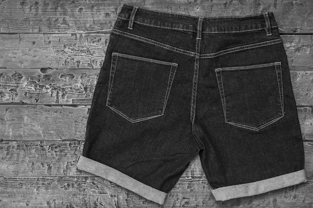 Immagine in bianco e nero di shorts in denim con polsini su fondo in legno