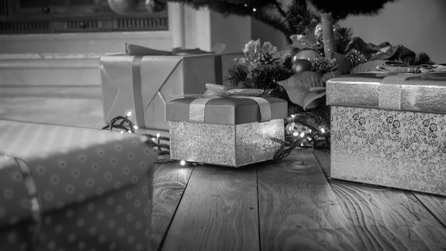 Immagine in bianco e nero di regali in scatole sul pavimento di legno sotto l'albero di natale
