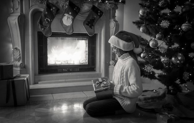 Immagine in bianco e nero di una ragazza che tiene in mano una scatola regalo e si siede accanto al caminetto e albero di natale decorato