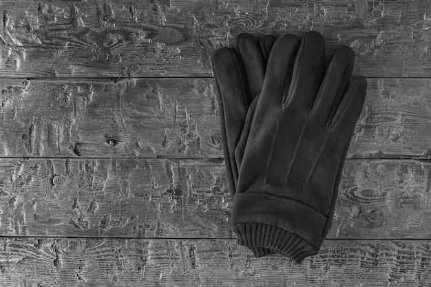 Immagine in bianco e nero di guanti da uomo in pelle sulla tavola di legno. accessorio da uomo per il clima fresco. vista dall'alto.