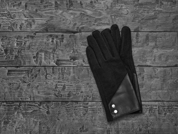 Immagine in bianco e nero di guanti da donna su un tavolo di legno
