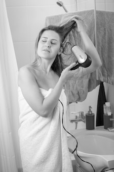 Immagine in bianco e nero di una giovane donna con asciugacapelli allo specchio del bagno