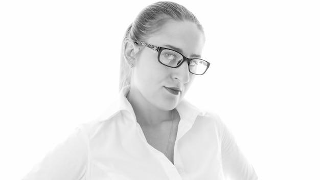 Ritratto isolato in bianco e nero di giovane donna in camicetta bianca e occhiali da vista.
