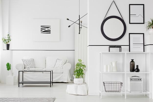 Interno del soggiorno in bianco e nero con divano, tavolo, scaffali, ornamenti, poster e piante