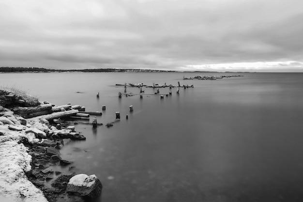 Paesaggio minimalista in bianco e nero con un vecchio molo in rovina nell'artico