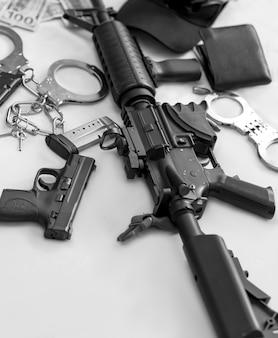 Bianco e nero del fucile automatico moderno, manette della polizia d'argento, portafoglio, pistola semiautomatica pistola pistola arma da fuoco con riviste e occhiali da sole su banconote in dollari americani. criminalità, mafia, terrorismo