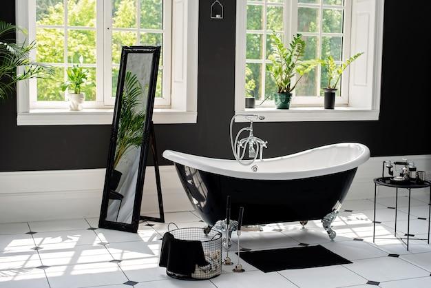 Bagno moderno in bianco e nero con rifiniture argentate con ampie finestre soleggiate. concetto di interior design
