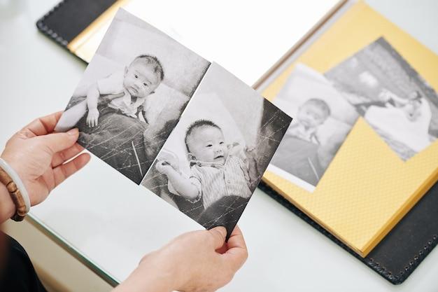 Vecchie foto in bianco e nero nelle mani di una donna matura, vista dall'alto