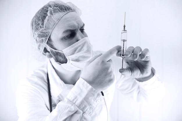 Foto in bianco e nero di un medico barbuto in camice bianco e una vecchia siringa