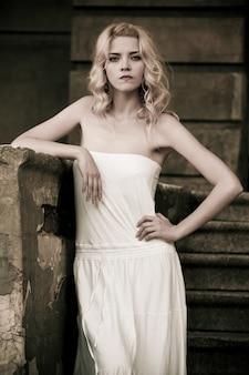 Foto in bianco e nero di una giovane e bella donna in abito bianco che scende le scale sullo sfondo di un vecchio edificio con porte. concetto di romanticismo gotico