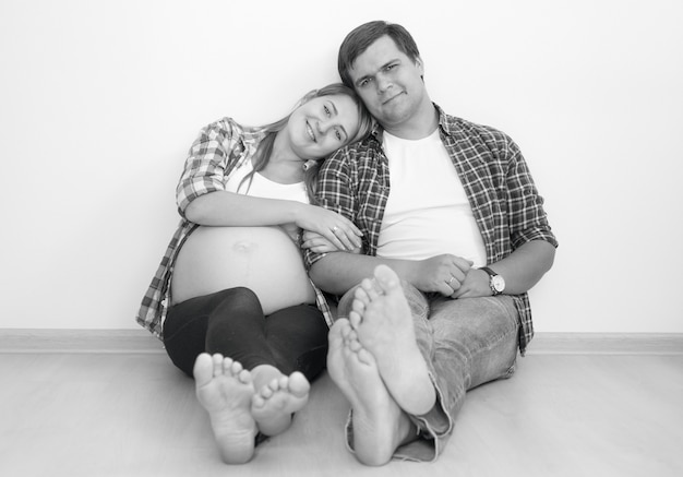 Foto in bianco e nero di una coppia incinta felice che si abbraccia sul pavimento